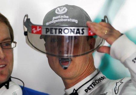 Михаэль Шумахер держит забрало его шлема